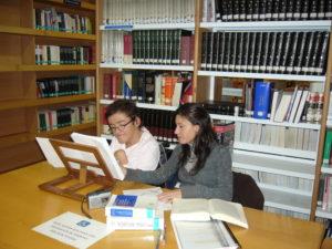 Dos personas, una de ellas con discapacidad, estudiando en una biblioteca.