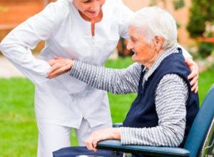 Una cuidadora ayuda a una mujer mayor a levantarse