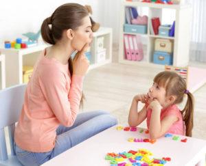 Una mujer enseña a una niña ejercicios de dicción.