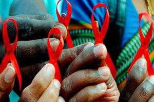 Varias manos de mujer sujetan un lazo rojo