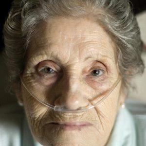 Mujer mayor con tubo de ox'geno.