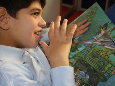 Jaime fascinado con las imágenes de su libro favorito; toca las hojas del libro acariciándolas. (Foto presentada a la edición 8 del  Concurso de Fotografía Digital del INICO - Fundación Grupo Norte)