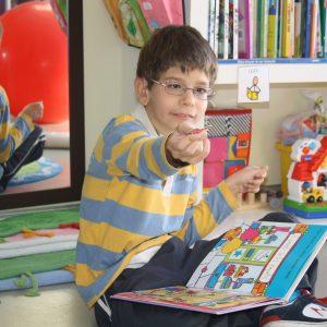 David buscando figuras desplegables en un libro y entregando la que se le pide. (Foto presentada a la edición 8 del  Concurso de Fotografía Digital del INICO - Fundación Grupo Norte)