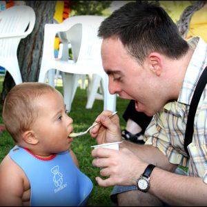 Joven con Síndrome de Down ayudando a comer a un niño con Síndrome de Down (Foto presentada a la edición 9 del  Concurso de Fotografía Digital del INICO - Fundación Grupo Norte)