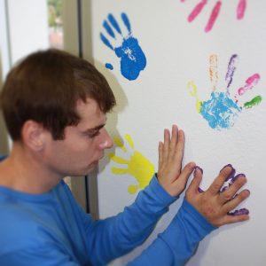 persona con autismo decorando una pared (Foto presentada a la edición 10 del  Concurso de Fotografía Digital del INICO - Fundación Grupo Norte)