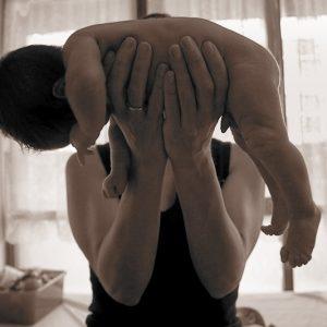 Una mujer sujeta en sus manos a un bebe recién nacido