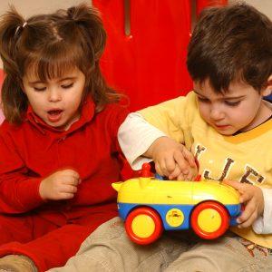 Una niña invidente esta juegando con su amigo, éste la muestra como es su coche de juguete. (Foto presentada a la edición 7 del  Concurso de Fotografía Digital del INICO - Fundación Grupo Norte)