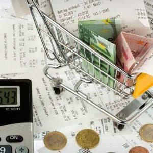 calculadora, dinero y una cesta de la compra. Imagen alusiva al gasto familiar