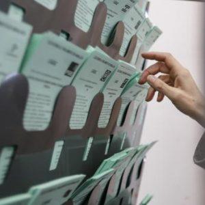 Una mano selecciona varias papeletas en unas elecciones.