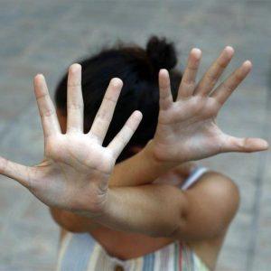 Una mujer se defiende cruzando los brazos delante de su cara