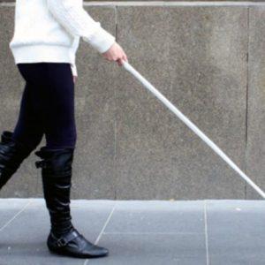 mujer con discapacidad visual camina con la ayuda de un bastón