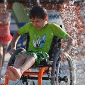 niño en una silla de ruedas disfrutando en un parque temático, ocio