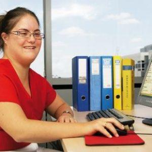 mujer con discapacidad trabajando con un ordenador